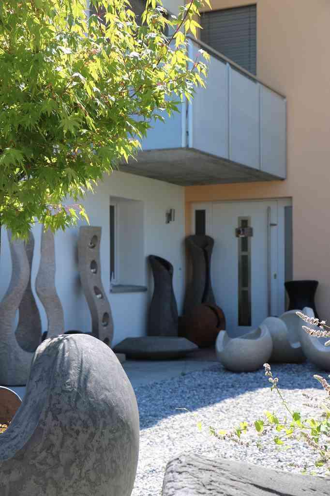 Diverse Skulpturen vor Eingang, mit Sonne